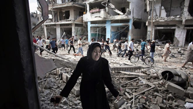 A Palestinian woman reacts after seeing her destroyed house during a 12-hour cease-fire in Gaza City's Shijaiyah neighborhood on July 26, 2014.