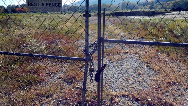 Land behind this gate in Swannanoa was once home to Beacon Manufacturing, for decades one of Buncombe County's largest employers. Foreign competition contributed to its closure. The empty plant burned in 2003.