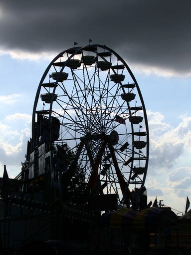 The Ferris wheel is silhouetted against a cloudy sky as the Cajun Heartland State fair continues Saturday, May 24, 2014, outside the Cajundome in Lafayette, La.