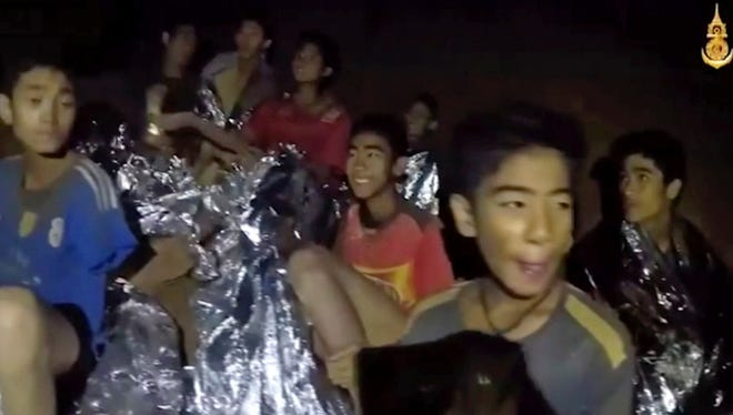 In this July 3, 2018, image taken from video provided by the Royal Thai Navy Facebook Page, a Thai boy smiles as a Thai Navy SEAL medic helps injured children inside a cave in Mae Sai, northern Thailand.