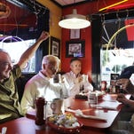 Democratic vice presidential candidate Sen. Tim Kaine of Virginia, left, cheers while talking about sports over breakfast with friends at City Diner Tuesday in Richmond, Virginia.