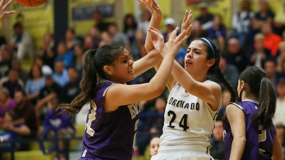 Coronado's Abigail Bumgardner, center, passes over Burges defender Anika Galindo Tuesday.