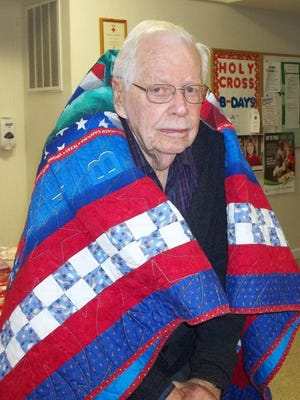 Irving Bernard, a WWII veteran of the US Army Air Corps, was recently awarded a Quilt of Valor by the Mountain Home Quilts of Valor. The award was made during a reception for veterans at Holy Cross Lutheran Church in Mountain Home.