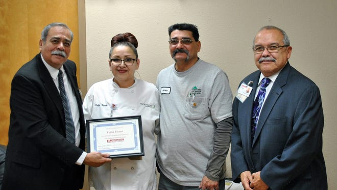 Velia Fierro was recognized by the Gila Regional Medical Center Board for spending 20 years in Dietary. Above, she poses with her award with Chair of the board Jeremiah Garcia, left, her husband James Fierro and CEO of GRMC Alfred Ontiveros, far right.