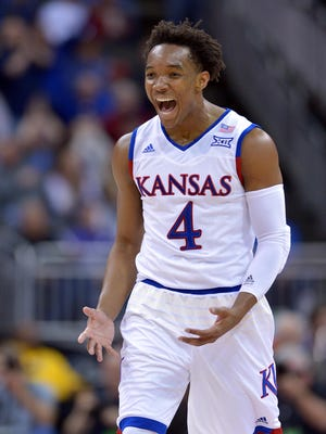Kansas Jayhawks guard Devonte' Graham (4) celebrates after making a three point basket against the Kansas State Wildcats in the first half during the Big 12 Conference tournament at Sprint Center.