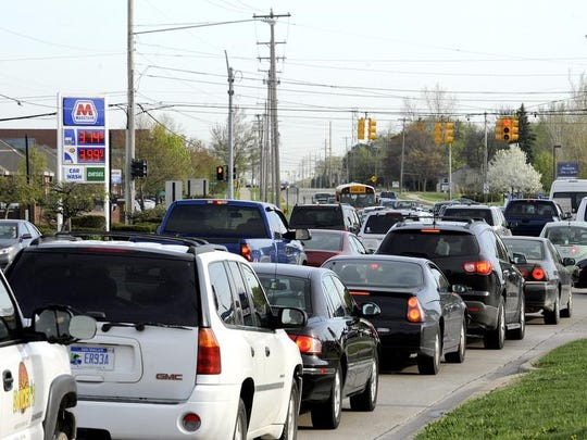 Traffic at Okemos and Jolly Roads on a busy Monday morning in 2013. UberX service that recently arrived in Greater Lansing allows private individuals to offer rides in their own vehicles, connecting with customers via Uber's smartphone apps and Web page.
