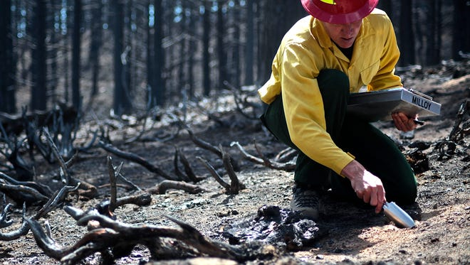 Eric Schroder, U.S. Forest Service Burned Area Emergency Response team's, soil scientist, tests water absorption levels of the burned ground that indicate potential flood capacity, at the Lake Fire site in the San Bernardino National Forest Sunday.