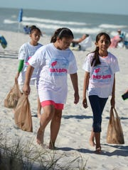 Volunteers from Avalon Elementary return to Lowdermilk Park with bags full of trash. About 1,500 volunteers hit Collier County beaches - and canals, shorelines and related areas - on Saturday, April 8, for Bay Days, a coasal cleanup that it part of a national effort.