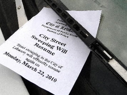 A 2010 reminder tucked under a windshield wiper that street sweeping will resume in York. (FILE)