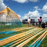 """Members of the group FR3FAL (pronounced Free-Fall) assemble shade areas they call """"shell-ters"""" on the edge of the great lawn on Wednesday afternoon in preparation of this weekend's Forecastle Fest."""