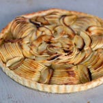 French apple tart in Concord, N.H. on Sept. 8, 2014. When slicing the apple stop each slice when you're still about 1/4 inch from the surface of the cutting board. According to chef Sara Moulton it is easier to slice an apple thinly when each slice remains attached at the bottom.