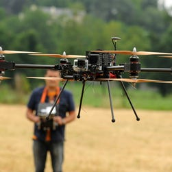 A man operates with a remote control 4-8X Dual Atex drone on June 6, 2015 in Pau, southwestern France. T