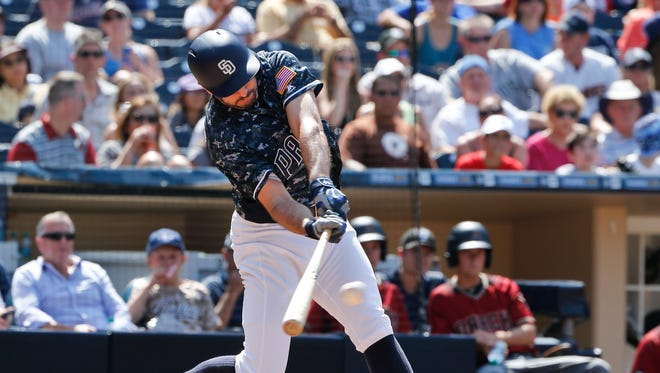 San Diego Padres' Adam Rosales connects to drive a triple to right center field and drive in a run against the Arizona Diamondbacks in the ffifth inning of a baseball game, Sunday, Aug. 21, 2016, in San Diego.
