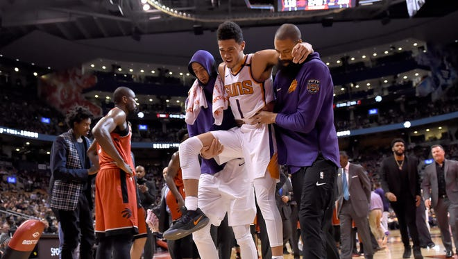 Phoenix Suns guard Devin Booker (1) is carried off by teammates during the second half of an NBA basketball game against the Toronto Raptors on Tuesday, Dec. 5, 2017, in Toronto.