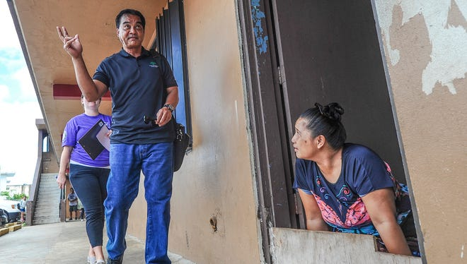 Federated States of Micronesia consulate employee Willie Williander and BIg Brothers Big Sisters's Kara Sexton approach tenant Edleen Fabian as she sits in the doorway of an apartment at the Hemlani's Harmon Apartments on Tuesday, July 19.