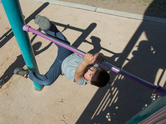 Nathaniel Holguin, 5, attempts to hang from the jungle gym at the Frank O'Brien Papen Community Center, Tuesday March 20, 2018, during the Spring Break Camp organized by the City of Las Cruces Parks and Recreation Department.