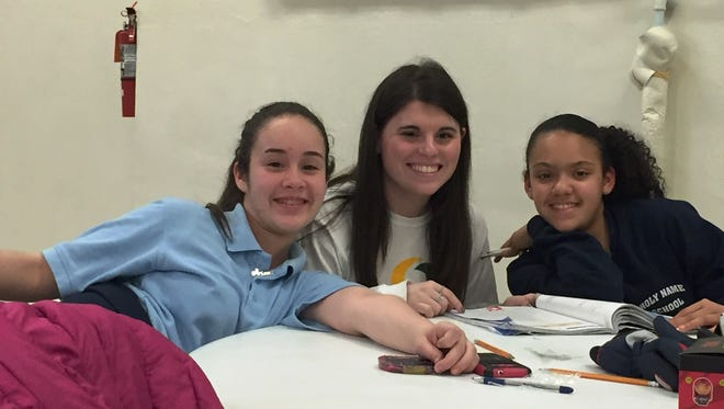 Olivia Marrone, a senior at Our Lady of Mercy Academy, helps students at Holy Name School in Camden with their homework during a recent visit.