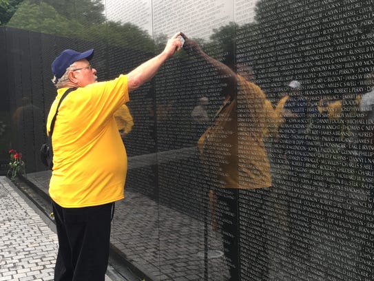 Vietnam veteran Russell Iwin  touches a name on the