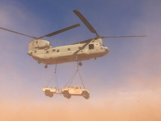 A Chinook helicopter lifts a Humvee and attached trailer