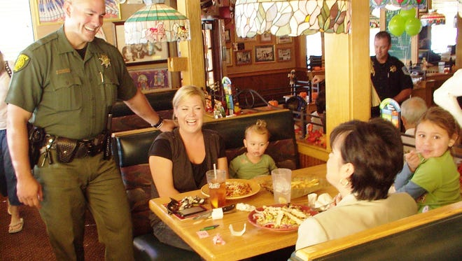 A file photo of Washoe County Sheriff's Deputy Armando Avina chating with customers at a Tip a Cop event held in 2010.  Law enforcement officers helped serve lunch and dinner at a restaurants statewide to raise money for Nevada's Special Olympic athletes.