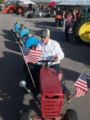 Bud Derman, a local farmer, give the kids a ride in the cart train, pulled by his antique tractor, as part of Ag Day outside Aggie Memorial Stadium. Ag Day was part of the tailgating festivities Saturday, Oct. 28, 2017.