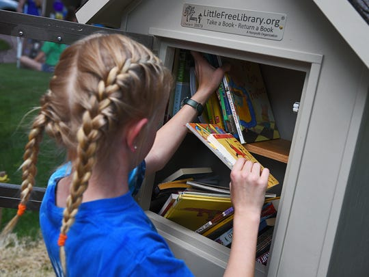 "Nora Boetel, 9, organizes books in her free library during a ""grand opening"" for her free library Monday, June 13, 2016, outside her house in Sioux Falls."