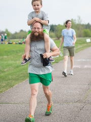 Carlo Amann-Burns, 4, of Hamilton, N.Y, gets a shoulder ride from his dad Jerry Amann-Burns at the annual VNA's Vermont Respite House 5K Fun Run & Jiggety Jog in Williston. The family was participating in honor of Gino Moretti, the family patriarch.