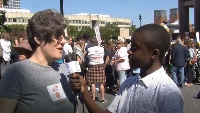 Jesse Givens speaks with a participant at the Sept. 20 youth climate strike in Boston as part of a Brookline Interactive Group documentary.
