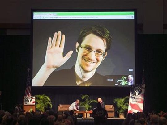 In this Feb. 14, 2015, file photo, Edward Snowden appears on a live video feed broadcast from Moscow at an event sponsored by ACLU Hawaii in Honolulu.