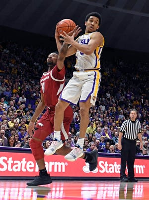 Arkansas guard Keyshawn Embery-Simpson (11) gets a hand on the ball to knock the rebound loose from LSU guard Tremont Waters (3) during the second half of an NCAA college basketball game Saturday, Feb. 2, 2019, in Baton Rouge, La. Arkansas won 90-89. (AP Photo/Bill Feig)