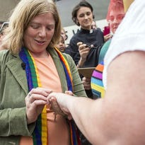 Amy Cantrell places the wedding ring on partner Lauren White's finger during their ceremony on the steps of the Buncombe County Register of Deeds office in Asheville in 2014.