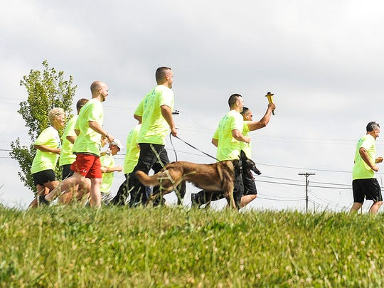 Law enforcement officers along with prison staff begin their 1.3-mile journey with the Special Olympics Torch from the Multi-County Correctional Center to the North Central Correctional Institute.