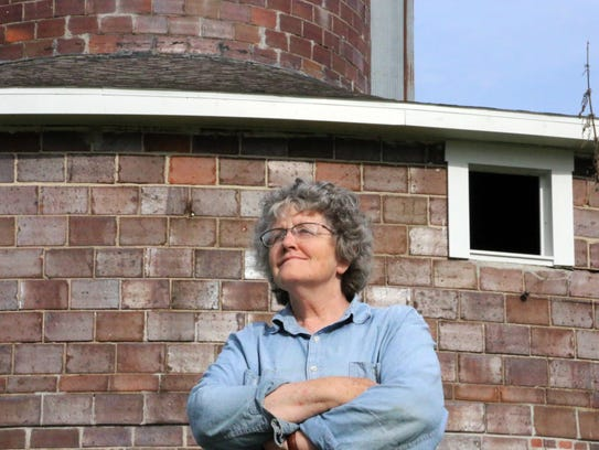 Loie Hayward stands in front of her brick barn, built