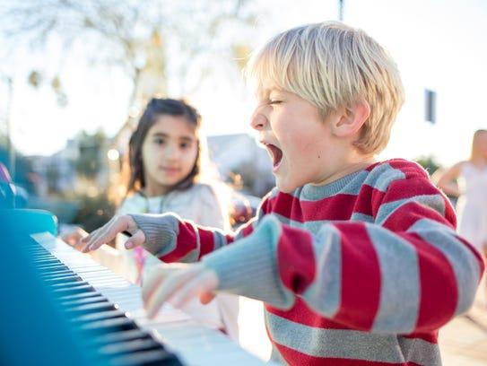 Visitors play a street piano at the Mesa Arts Center