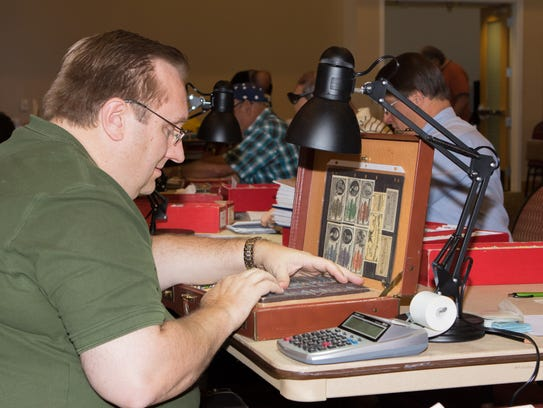 Stamp dealer Michael Ball of Phoenix peruses his collection