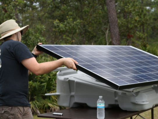 Rubin York carries one of the solar panels during the