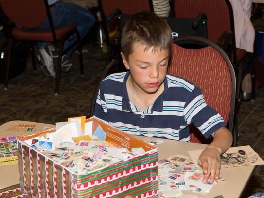 Joe Armstrong, an 8-year-old stamp enthusiast, checks