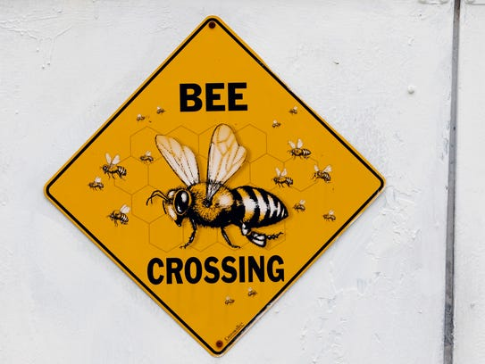 A sign tells people there are bees around one of the