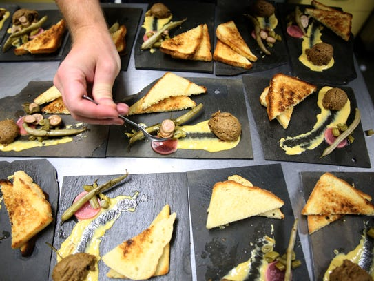 Volunteers help plate a dish of Spanish style woodland