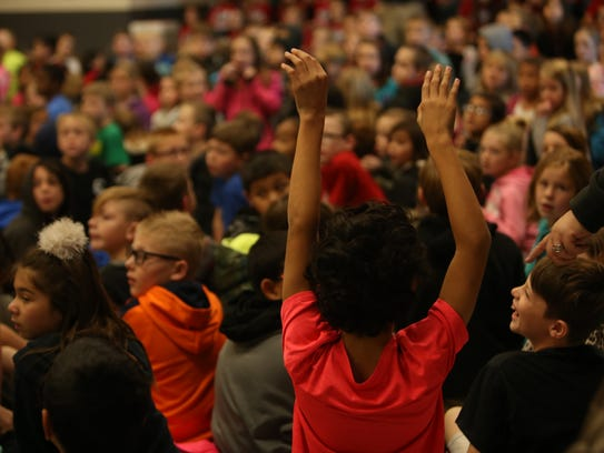 A Hurricane Elementary School student sits in an assembly.