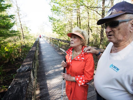 CREW volunteer Bob Melin, right, describes the swamp