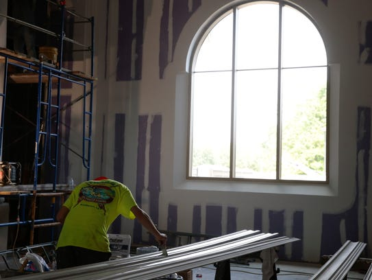 A worker paints molding inside the new St. Pius X Church