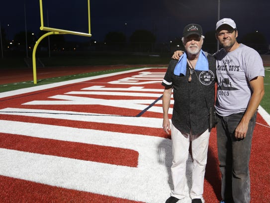 Merrill and Justin Osmond pose in the end zone at Legend