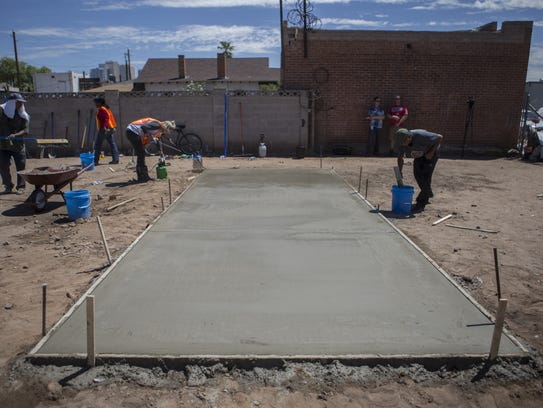 Volunteers level the concrete base for one of two tiny