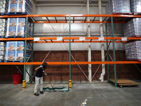 A Costco worker sweeps under the empty shelves where