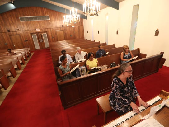 D.L. Laseur leads the choir during rehearsal at St.