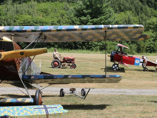 A replica Fokker Dr 1 triplane is towed into position