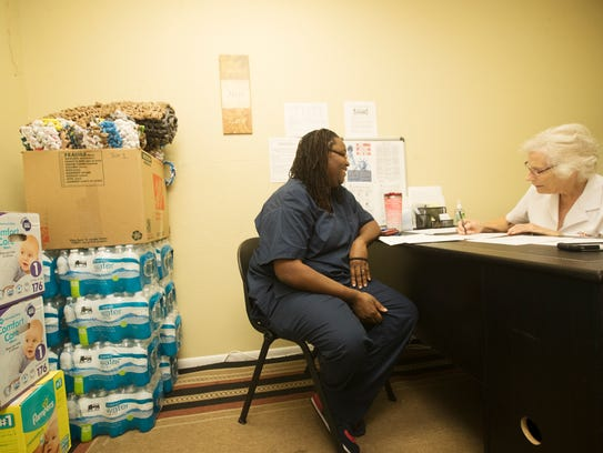 Latoya Smith, left, signs up for the Salvation Army