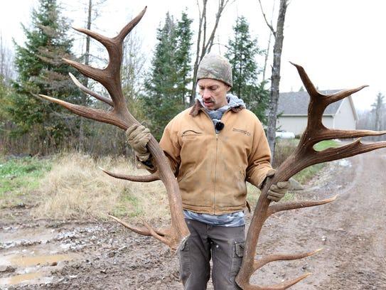 Rick Ewert holds up a pair of elk antlers at Hemlock