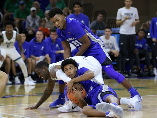 FGCU's Zach Johnson fights for possession during Florida Gulf Coast's second meeting with Middle Tennessee State this season on Saturday  at Alico Arena.